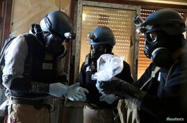 A U.N. chemical weapons expert, wearing a gas mask, holds a plastic bag containing samples from one of the sites of an alleged chemical weapons attack in the Ain Tarma neighborhood of Damascus. A team of U.N. experts left their Damascus hotel for a thi...
