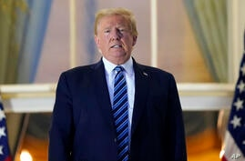 President Donald Trump stands on the balcony outside of the Blue Room as returns to the White House Monday, Oct. 5, 2020, in…