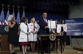 WASHINGTON, DC - JULY 24: U.S. President Donald Trump signs executive orders on prescription drug prices in the South Court…
