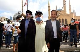 A man poses for a picture with a cardboard cut-out of Hassan Nasrallah (L), the head of Lebanon's Shiite Muslim movement…