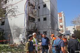 Israeli rescue teams inspect the damage outside a building which received a direct hit by rockets from the Gaza Strip, in the…