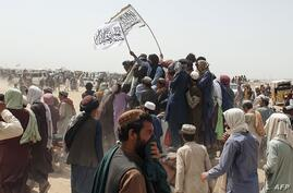 People wave Taliban flags as they drive through the Pakistani border town of Chaman on July 14, 2021, after the Taliban claimed…