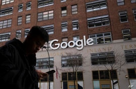 A man using a mobile phone walks past Google offices, Monday, Dec. 17, 2018, in New York. (AP Photo/Mark Lennihan)