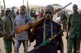 FILE - In this Wednesday Nov. 25, 2014 file photo, hunters gather during a meeting in Yolo, Nigeria. Thousands of Nigerian…
