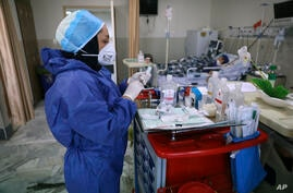 In this Tuesday, June 16, 2020, photo, a nurse prepares medicines for COVID-19 patients at the Shohadaye Tajrish Hospital in…