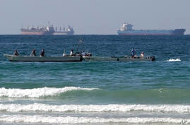 FILE - In this Jan. 19, 2012 file photo, fishing boats are seen in front of oil tankers on the Persian Gulf waters, south of…