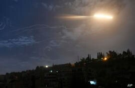 In this photo released by the Syrian official news agency SANA, shows missiles flying into the sky near international airport,…