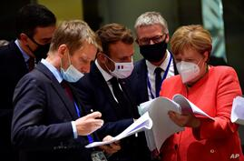 German Chancellor Angela Merkel, right, speaks with French President Emmanuel Macron, center, during a round table meeting at…