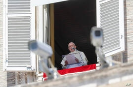 Pope Francis, framed by security cameras, delivers his blessing as he recites the Angelus noon prayer from the window of his…
