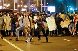 Demonstrators run away from police as they gather to protest against a result of the Belarusian presidential election in Minsk,…