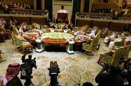Cameramen film Saudi King Salman, center, as he chairs the 40th Gulf Cooperation Council (GCC) Summit in Riyadh, Saudi Arabia,…