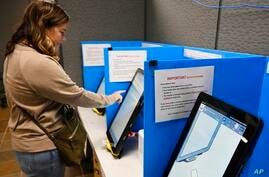 FILE-In this Tuesday, Nov. 5, 2019 file photoCourtney Parker votes on a new voting machine, in Dallas, Ga. Voting integrity…