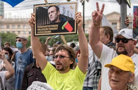 """A man holds a poster with a portrait of Alexei Navalny reading """"Navalny was poisoned, we know who is to blame, Alexei you must…"""