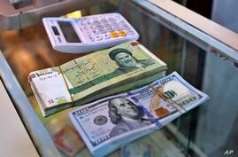 In this Wednesday, May 21, 2019, photo, U.S. and Iranian currency are readied by a money exchanger outside the golden-domed…
