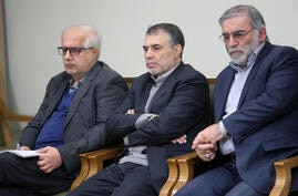 In this picture released by the official website of the office of the Iranian supreme leader, Mohsen Fakhrizadeh, right, sits…