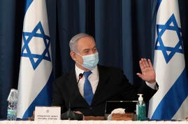 Israeli Prime Minister Benjamin Netanyahu wears a face mask to help prevent the spread of the coronavirus as he chairs the…