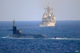 In this photo made available by the U.S. Navy, the guided-missile submarine USS Georgia, front, with the guided-missile cruiser…