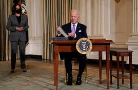 President Joe Biden signs executive orders in the State Dining Room of the White House, Tuesday, Jan. 26, 2021, in Washington…
