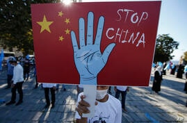 FILE - In this file photo taken Thursday, Oct. 1, 2020, a protester from the Uighur community living in Turkey, holds an anti…