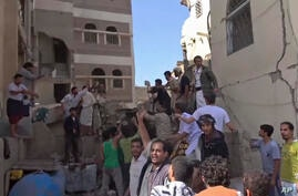 In this frame grab from from video, people search in the rubble following Saudi-led coalition airstrikes that killed at least…