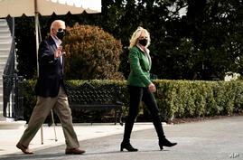 President Joe Biden and first lady Jill Biden walk across the South Lawn to board Marine One at the White House in Washington,…