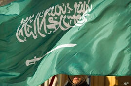 FILE - In this March 22, 2018, file photo, an honor guard member is covered by the flag of Saudi Arabia, in Washington. Three…