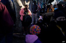 A woman seeking asylum in the United States waits with others for news of policy changes, Friday, Feb. 19, 2021, in Tijuana,…