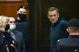 In this handout photo provided by Moscow City Court Russian opposition leader Alexei Navalny talks to his lawyers standing in…