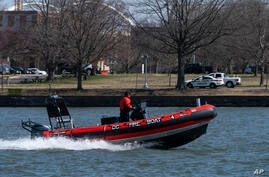 In this Friday March 19, 2021, photo a District of Columbia Fire Boat checks buoys in the waterway next to Fort McNair, seen in…