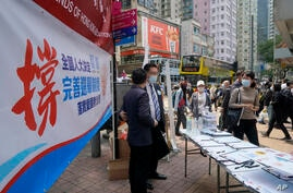Pro-China staff members collect resident's signature at a stall to support a proposal to draft changes of election rules for…