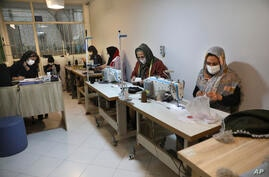 Women sew protective face masks at a workshop of Bavar charity in Tehran, Iran, Monday, Nov. 23, 2020. As the coronavirus…