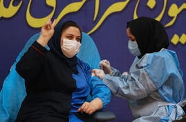 Sara Goudarzi, a nurse from the Imam Khomeini Hospital flashes a victory sign as she receives a Russian Sputnik V coronavirus…