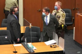 In this image from video, former Minneapolis police Officer Derek Chauvin, center, is taken into custody as his attorney, Eric…