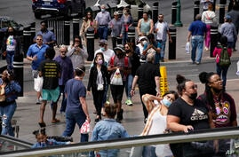 Masked and unmasked pedestrians walk along the Las Vegas Strip, Tuesday, April 27, 2021, in Las Vegas. The Centers for Disease…