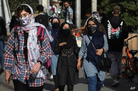 People wear protective face masks to help prevent the spread of the coronavirus in downtown Tehran, Iran, Monday, April 5, 2021…