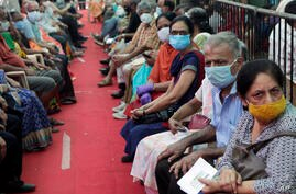 People wait to receive COVID-19 vaccine in Mumbai, India, Thursday, April 29, 2021. India set another global record in new…