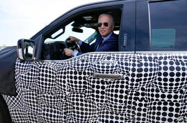 President Joe Biden stops to talk to the media as he drives a Ford F-150 Lightning truck at Ford Dearborn Development Center,…