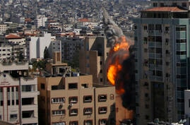 An Israeli airstrike hits the high-rise building housing The Associated Press' offices in Gaza City, Saturday, May 15, 2021. …