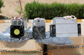 """This undated photo provided by the Police News Agency, shows boxes of machinery used in Bitcoin """"mining"""" operations that were…"""