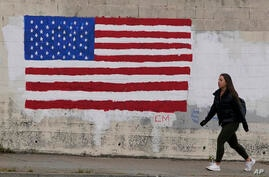 FILE - In this May 13, 2021, file photo, pedestrian walks in front of an American flag painted on a wall during the coronavirus…