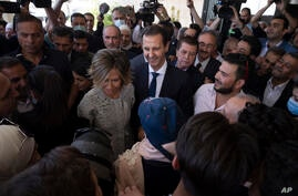 Syrian President Bashar Assad and his wife Asma meet Syrian citizens after they vote at a polling station during the…