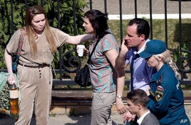 A Russian emergency employee and a woman try to comfort a couple on their way to an ambulance at a school after a shooting in…