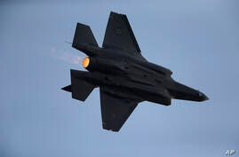 An Israeli Air Force F-35 plane performs during a graduation ceremony for new pilots in the Hatzerim air force base near the…