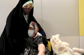 An Iranian woman receives a Sinopharm vaccine for COVID-19 at the Iran Mall shopping center, in Tehran, Iran, Monday, May 17,…