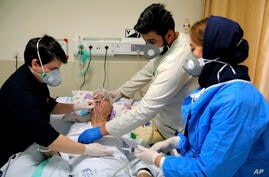Medical personnel tend to a COVID-19 patient at the Shohadaye Tajrish Hospital in Tehran, Iran, Saturday, April 17, 2021. After…