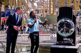 California Governor Gavin Newsom, left, looks on as Access Hollywood personality Scott Evans draws a ball with a winning number…