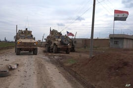 In this frame grab from video, an American military convoy is seen in the village of Khirbet Ammu, east of Qamishli city, Syria…