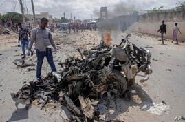 Security forces and civilians gather near the wreckage after a suicide car bomb attack that targeted the city's police…