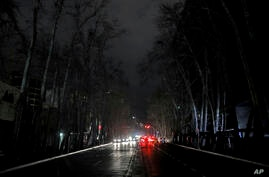 Cars drive on an unlit street during a blackout in Tehran, Iran, Wednesday, Jan 20, 2021. Speculation has gripped social media…