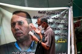 FILE - In this July 12, 2020 file photo, a protester prays by a poster showing Hisham al-Hashimi an Iraqi analyst who was a…